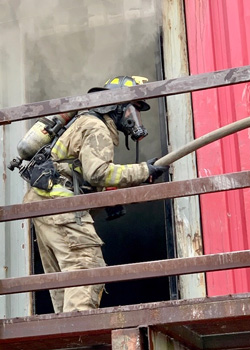Firefighter training, firefighter with ventilator on outside a burning structure
