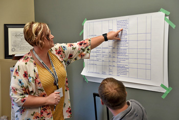 Woman pointing to table of info on a wall