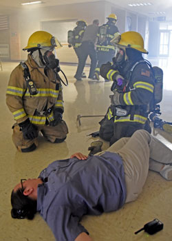 Firefighter training exercise with victim on floor and victim being assisted outside