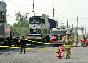 Firefighters and other personnel working near caution tape around train