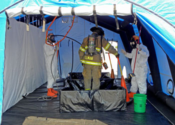 Firefighter training in hazmat tent with masks