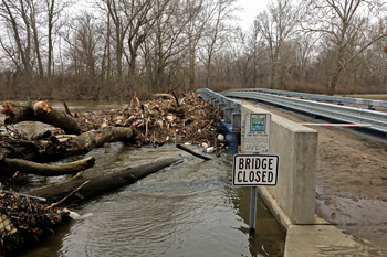 Log jam with debris against closed bridge