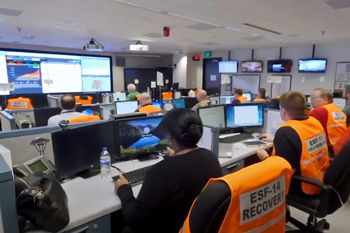 People at computer stations in control room