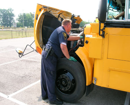 ISP CVED officer inspects a school bus engine.